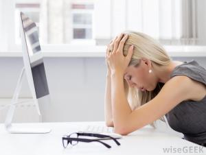 stressed-woman-with-blonde-hair-with-hands-on-head-near-computer