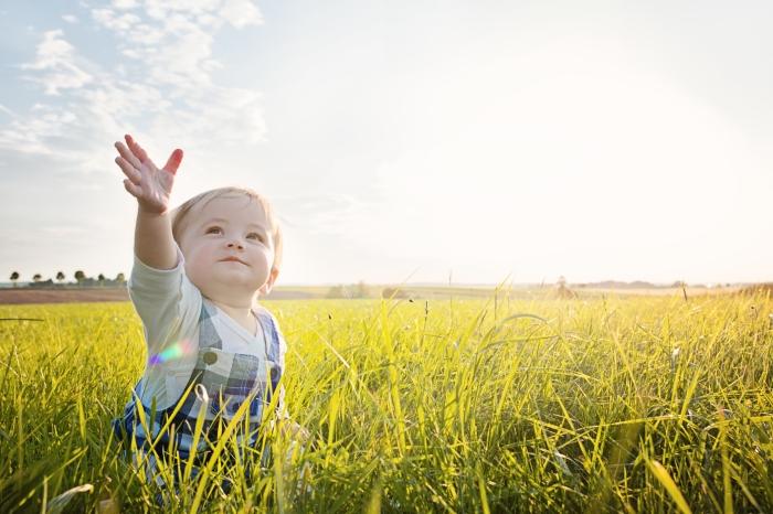 baby-sitting-in-grass-reaching-to-the-sky-1.jpg