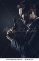 shutterstock stock-photo-brave-cool-man-holding-a-gun-on-dark-background-367738520