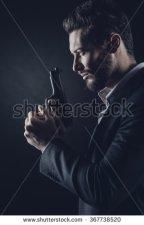 shutterstock stock-photo-brave-cool-man-holding-a-gun-on-dark-background-367738520