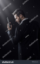 stock-photo-brave-cool-man-holding-a-gun-on-dark-background-288921608
