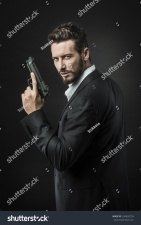stock-photo-confident-undercover-agent-with-a-gun-against-dark-background-246820759